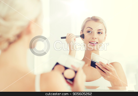 woman with makeup brush and foundation at bathroom stock photo, beauty, make up, cosmetics, morning and people concept - young woman with makeup brush and contouring and highlighting palette looking to mirror at home bathroom by Syda Productions