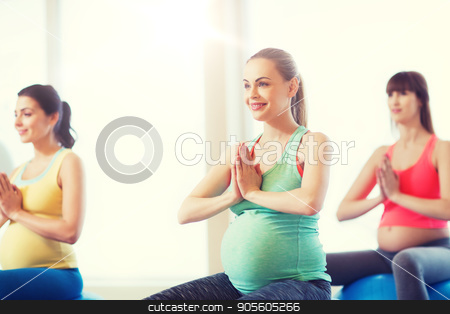 happy pregnant women exercising on fitball in gym stock photo, pregnancy, sport, fitness, people and healthy lifestyle concept - group of happy pregnant women exercising on ball in gym by Syda Productions