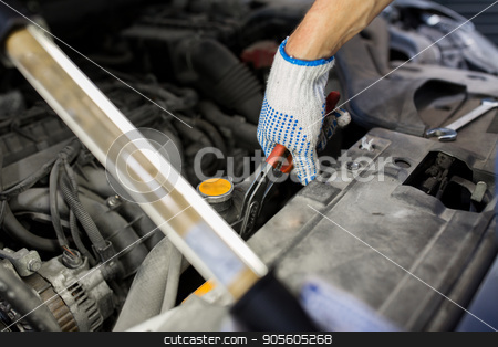 mechanic man with pliers repairing car at workshop stock photo, car service, repair, maintenance and people concept - auto mechanic man with lamp and pliers working at workshop by Syda Productions