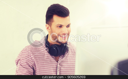 creative man with headphones and computer stock photo, business, startup, education, technology and people concept - happy creative man or student with headphones and computer at office by Syda Productions