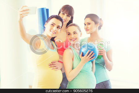 pregnant women taking selfie by smartphone in gym stock photo, pregnancy, sport, fitness, people and healthy lifestyle concept - group of happy pregnant women with sports stuff taking selfie by smartphone in gym by Syda Productions