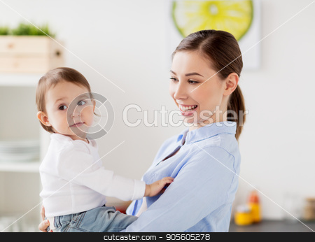 happy mother and little baby girl at home kitchen stock photo, family, food, eating, motherhood and people concept - happy mother and little baby girl at home kitchen by Syda Productions
