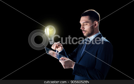 businessman with tablet pc and lightbulb stock photo, business, people, startup idea, inspiration and modern technology concept - businessman in suit working with transparent tablet pc computer and lightbulb over black background by Syda Productions