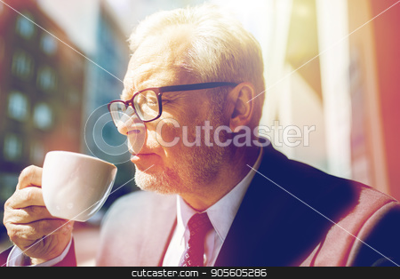 senior businessman drinking coffee on city street stock photo, business, hot drinks, break and people and concept - senior businessman drinking coffee from cup on city street by Syda Productions