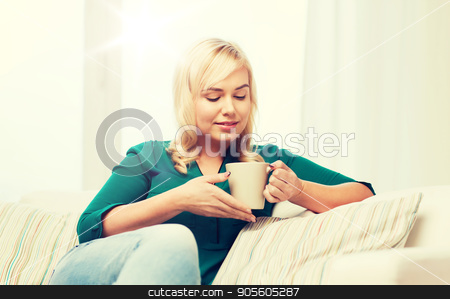 happy young woman at home stock photo, people and leisure concept - happy young woman sitting on sofa at home by Syda Productions