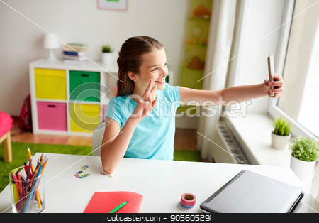 happy girl with smartphone taking selfie at home stock photo, people, children and technology concept - girl with laptop computer and smartphone taking selfie at home by Syda Productions