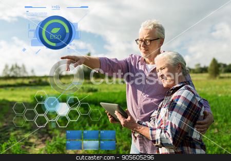 happy senior couple with tablet pc at summer farm stock photo, organic farming, gardening, agriculture and people concept - happy senior couple with tablet pc computer at summer farm by Syda Productions