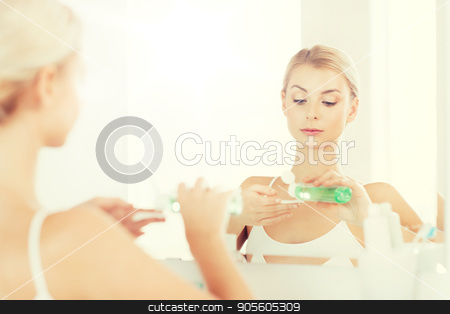 young woman with lotion washing face at bathroom stock photo, beauty, skin care and people concept - young woman applying lotion to cotton disc for washing her face at bathroom by Syda Productions