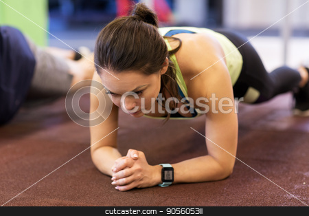 woman with heart-rate tracker exercising in gym stock photo, fitness, sport, exercising and people concept - woman with heart-rate tracker at group training doing plank exercise in gym by Syda Productions
