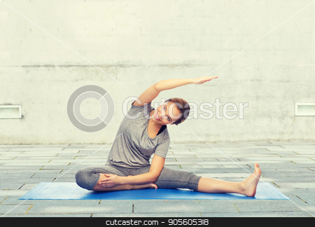 happy woman making yoga and stretching on mat stock photo, fitness, sport, people and healthy lifestyle concept - happy woman making yoga and stretching on mat over urban street background by Syda Productions