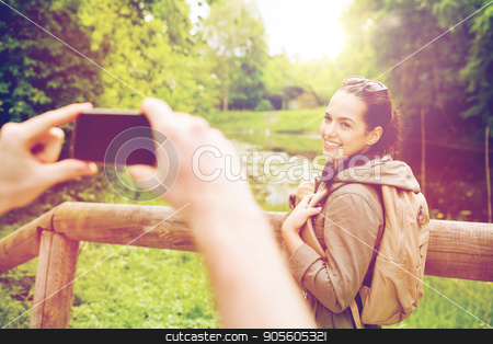 couple with backpacks taking picture by smartphone stock photo, travel, hiking, backpacking, tourism and people concept - smiling couple with backpacks taking picture by smartphone in nature by Syda Productions