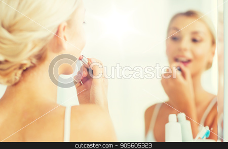 woman with lipstick applying make up at bathroom stock photo, beauty, make up, cosmetics, morning and people concept - smiling young woman applying lipstick and looking to mirror at home bathroom by Syda Productions