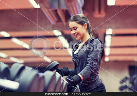 young smiling woman choosing dumbbells in gym stock photo, fitness, sport, exercising, weightlifting and people concept - young smiling woman choosing dumbbells in gym by Syda Productions
