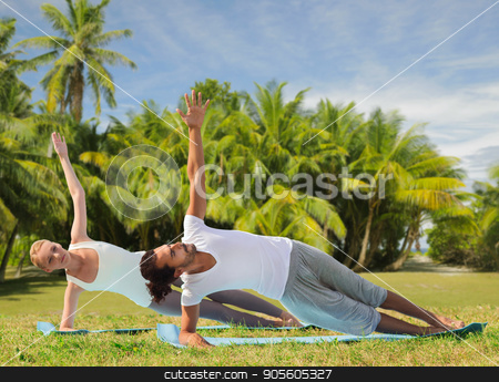 happy couple making yoga exercises on beach stock photo, fitness, sport and people concept - happy couple making yoga and meditating over exotic natural background with palm trees by Syda Productions