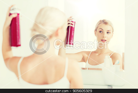 woman with hairspray styling her hair at bathroom stock photo, beauty, hygiene, hairstyle, morning and people concept - young woman with hairspray styling her hair and looking to mirror at home bathroom by Syda Productions