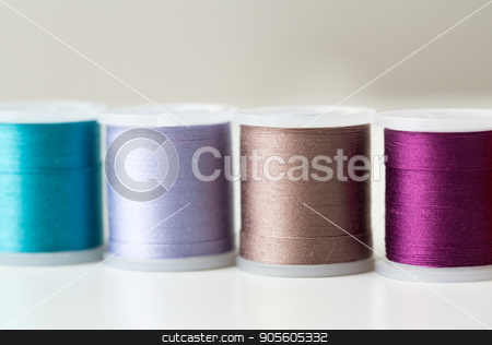 row of colorful thread spools on table stock photo, needlework, craft, sewing and tailoring concept - row of colorful thread spools on table by Syda Productions