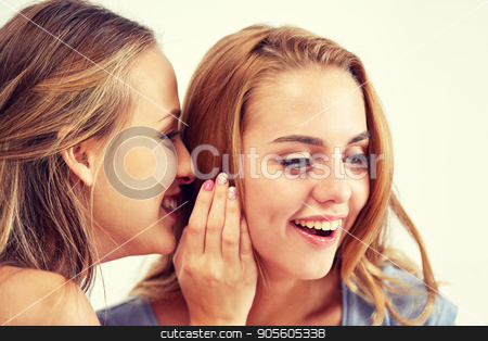 happy young women whispering gossip at home stock photo, friendship, people, pajama party and communication concept - happy young women gossiping and whispering to ear at home by Syda Productions