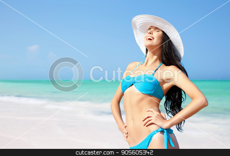 smiling young woman in sun hat on summer beach stock photo, summer holidays, vacation, travel and people concept - smiling young woman in bikini swimsuit and sun hat on beach over sea and blue sky background by Syda Productions