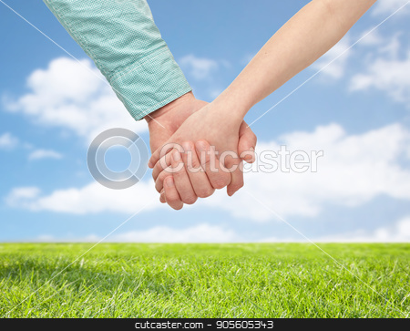 happy father and child holding hands stock photo, family and people concept - happy father and child holding hands over blue sky and grass background by Syda Productions