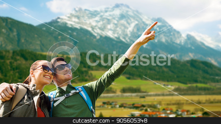 happy couple with backpacks traveling in highlands stock photo, travel, tourism and people concept - happy couple with backpacks outdoors pointing finger to something over mountains background by Syda Productions