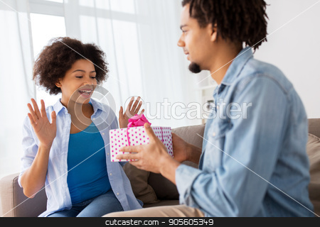 happy couple with gift box at home stock photo, family, holidays and people concept - happy couple with gift box at home by Syda Productions