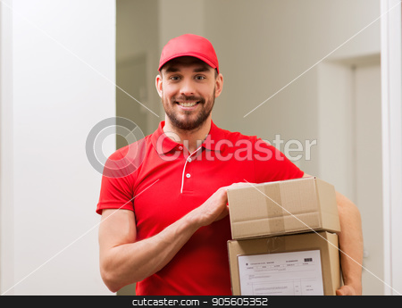 delivery man with parcel boxes in corridor stock photo, delivery, mail, people and shipment concept - happy man in red uniform with parcel boxes in corridor by Syda Productions
