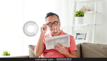 happy man in glasses reading newspaper at home stock photo, leisure, information, people and mass media concept - happy man in glasses reading newspaper at home by Syda Productions
