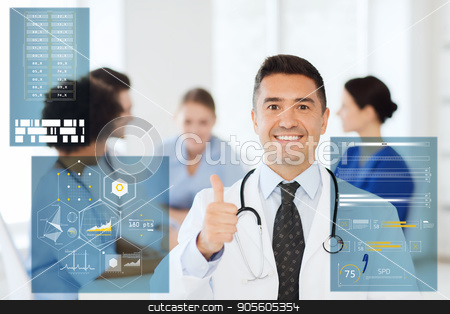 happy doctor showing thumbs up at hospital stock photo, medicine, healthcare, technology and people concept - happy male doctor over group of medics meeting at hospital showing thumbs up gesture by Syda Productions