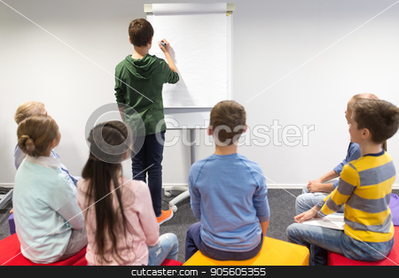 student boy with marker writing on flip board stock photo, education, elementary school, learning and people concept - student boy with marker writing on flip board by Syda Productions