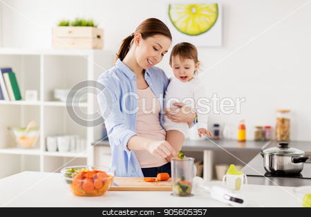 happy mother and baby cooking food at home kitchen stock photo, family, food, healthy eating, cooking and people concept - happy mother adding chopped vegetables to blender cup and holding little baby girl at home kitchen by Syda Productions