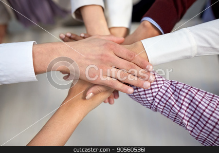 business team with hands on top at office stock photo, business, startup, gesture, people and teamwork concept - creative team with hands on top of each other at office by Syda Productions