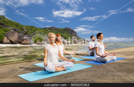 people meditating in yoga lotus pose outdoors stock photo, fitness, sport, yoga and healthy lifestyle concept - group of people meditating in lotus pose over exotic tropical beach background by Syda Productions