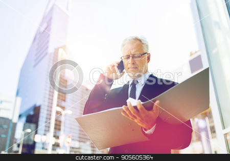 senior businessman calling on smartphone in city stock photo, business, technology, communication and people concept - senior businessman with document folder calling on smartphone in city by Syda Productions