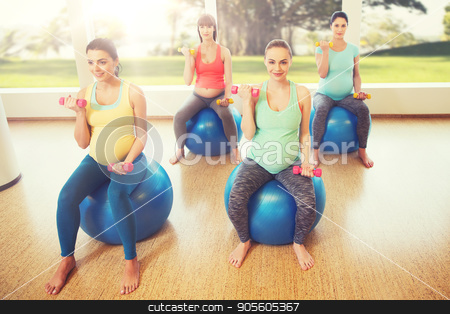 happy pregnant women exercising on fitball in gym stock photo, pregnancy, sport, fitness, people and healthy lifestyle concept - group of happy pregnant women with dumbbells exercising on ball in gym by Syda Productions