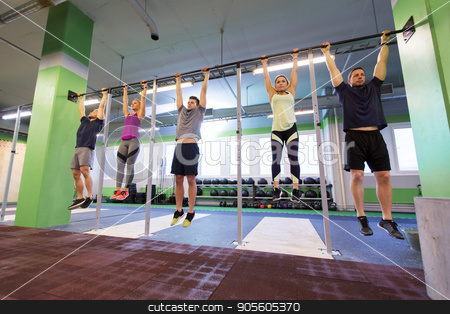 group of people hanging at horizontal bar in gym stock photo, sport, fitness, exercising and training concept - group of people hanging at horizontal bar in gym by Syda Productions