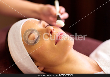beautician applying facial mask to woman at spa stock photo, people, beauty, cosmetology and treatment concept - close up of beautiful young woman lying with closed eyes and cosmetologist applying facial mask by brush at spa by Syda Productions