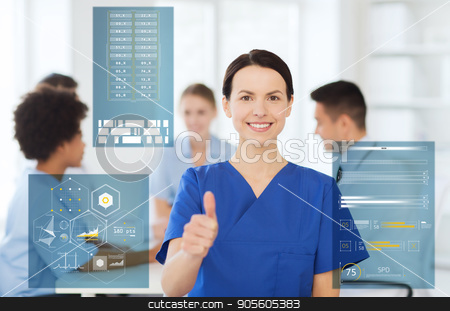 happy smiling doctor showing thumbs up at hospital stock photo, medicine, healthcare, technology and people concept - happy female doctor or nurse over group of medics meeting at hospital showing thumbs up gesture by Syda Productions