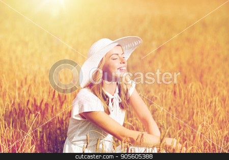 happy young woman in sun hat on cereal field stock photo, nature, summer holidays, vacation and people concept - happy young woman in white dress and sun hat enjoying sun on cereal field by Syda Productions