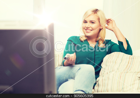 smiling woman with remote watching tv at home stock photo, television, leisure and people concept - smiling woman sitting on couch with remote control and watching tv at home by Syda Productions
