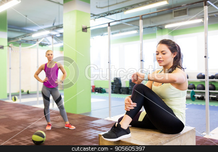 women with fitness tracker and ball in gym stock photo, sport, training and people concept - women with fitness tracker and medicine ball in gym by Syda Productions