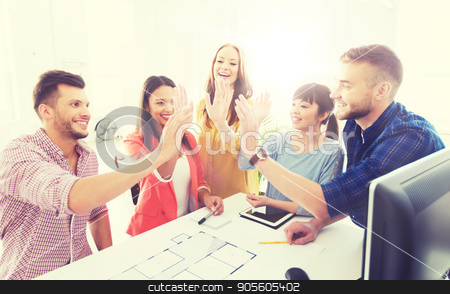 creative team making high five at office stock photo, business, startup, architecture, gesture and people concept - happy international creative architect team or students with blueprint making high five at office by Syda Productions