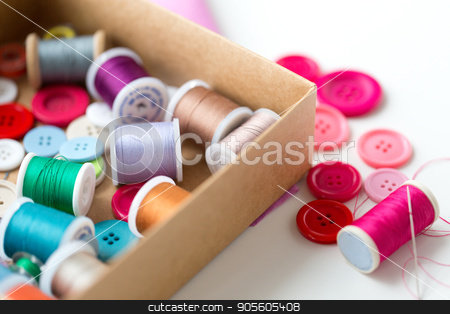 box with thread spools and sewing buttons on table stock photo, needlework, craft, sewing and tailoring concept - box with thread spools and buttons on table by Syda Productions