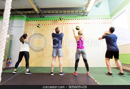 group of people with medicine ball training in gym stock photo, fitness, sport and exercising concept - group of people with medicine balls training in gym by Syda Productions