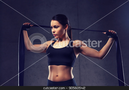 woman with expander exercising in gym stock photo, fitness, sport, training, people and lifestyle concept - woman doing exercises with expander or resistance band in gym by Syda Productions