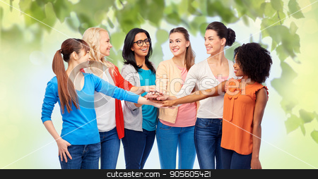 international group of women with hands together stock photo, diversity, race, ethnicity and people concept - international group of happy smiling different women holding hands together over green natural background by Syda Productions