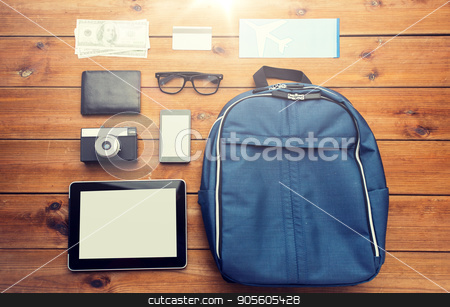close up of smartphone and travel stuff stock photo, travel, tourism, technology and objects concept - close up of smartphone with tablet pc computer, airplane ticket and personal stuff by Syda Productions