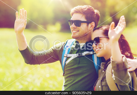 happy couple with backpacks hiking outdoors stock photo, travel, hiking, backpacking, tourism and people concept - happy couple with backpacks waving hands outdoors by Syda Productions