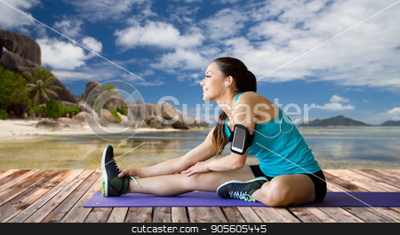 woman with smartphone stretching leg on mat stock photo, fitness, sport, exercising, technology and people concept - smiling woman wearing armband with smartphone and earphones stretching leg on mat over exotic tropical beach background by Syda Productions