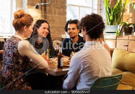 happy friends eating and drinking at bar or cafe stock photo, leisure, food, drinks, people and holidays concept - happy friends eating and drinking at bar or cafe by Syda Productions