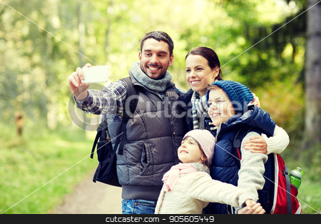 family taking selfie with smartphone in woods stock photo, travel, tourism, hike, technology and people concept - happy family with backpacks taking selfie by smartphone in woods by Syda Productions